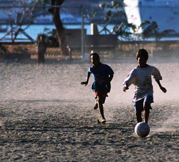 Grama Sintética - crianças jogando futebol
