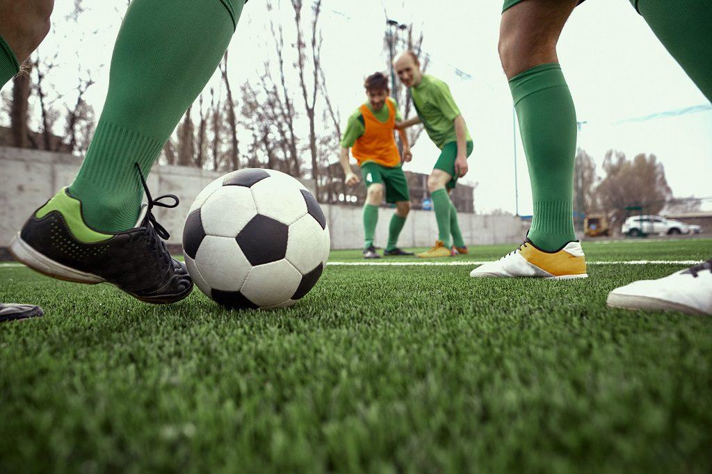 Jogadores da base em uma partida em um campo de grama sintética